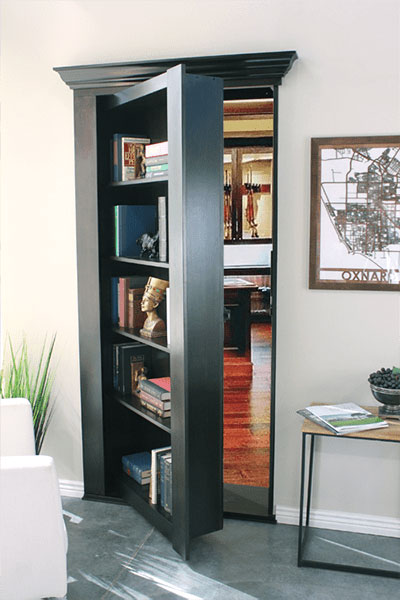Secret bookcase door halfway open showing secret room